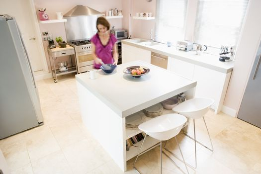 Woman in kitchen whisking on counter