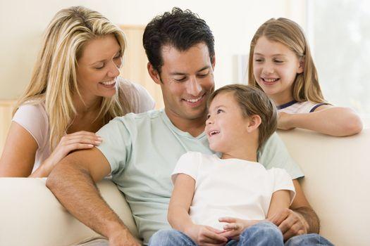 Family sitting in living room smiling