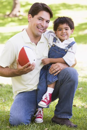 Man and young boy outdoors with football smiling
