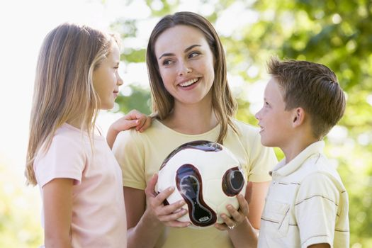 Woman and two young children outdoors holding volleyball and smi