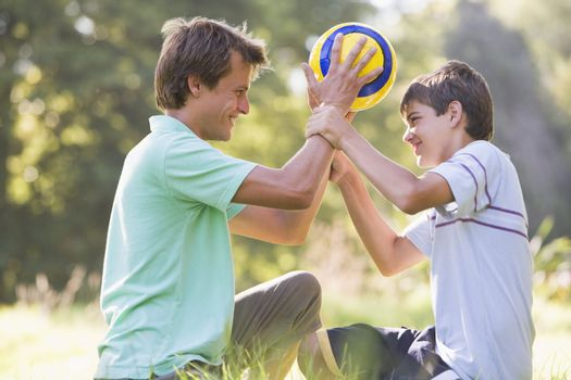 Man and young boy outdoors holding soccer ball and smiling