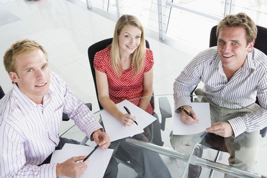 Three businesspeople in a boardroom with paperwork smiling