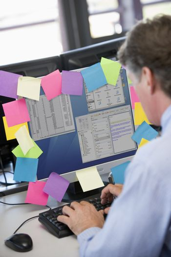 Businessman in office typing at computer with notes on it