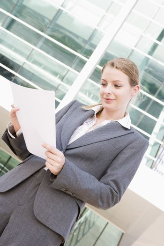 Businesswoman standing outdoors reading paperwork