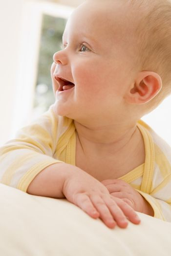 Baby lying indoors smiling