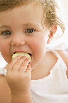 Baby indoors eating apple