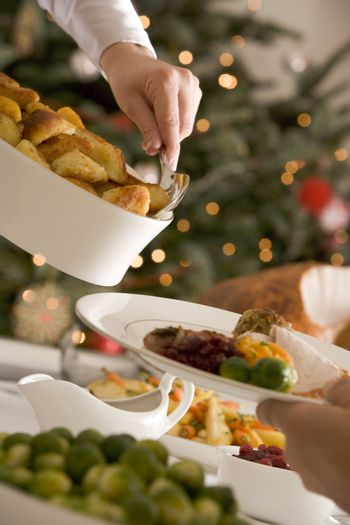 Serving Roast Potatoes at Christmas Lunch