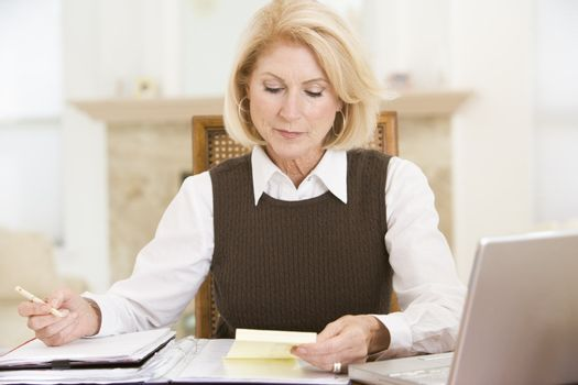 Woman in dining room with laptop and paperwork