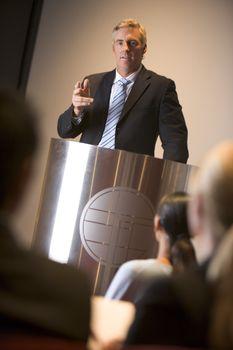 Businessman giving presentation at podium