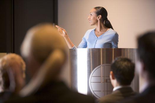 Businesswoman giving presentation at podium