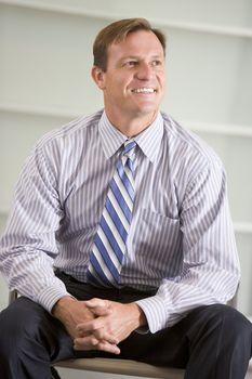 Businessman sitting indoors smiling
