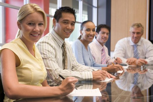 Five businesspeople in boardroom smiling