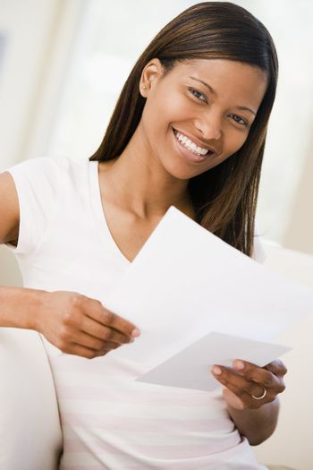 Woman in living room reading papers smiling