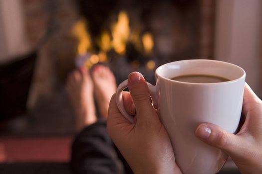 Feet warming at a fireplace with hands holding
