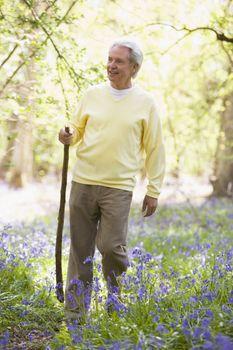 Man walking outdoors with walking stick smiling