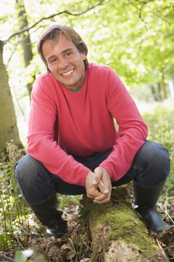 Man outdoors in woods sitting on log smiling