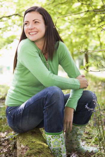 Woman outdoors in woods sitting on log smiling
