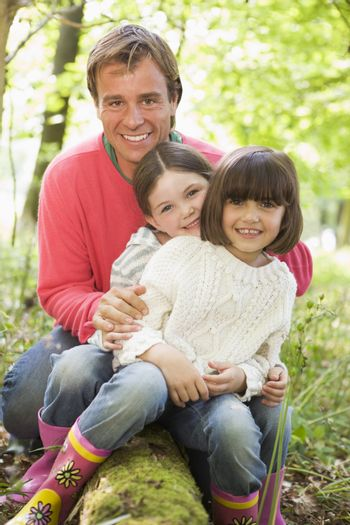Father and daughters outdoors in woods sitting on log smiling