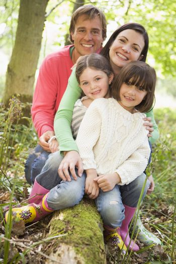 Family outdoors in woods sitting on log smiling