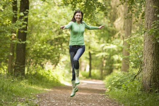 Woman jumping on path smiling