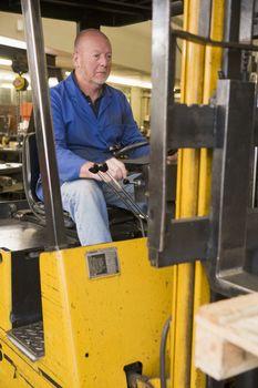 Warehouse worker in forklift