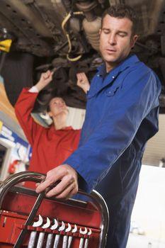 Two mechanics working under car
