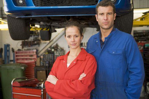 Two mechanics standing in garage