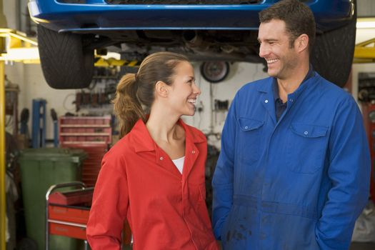 Two mechanics standing in garage smiling