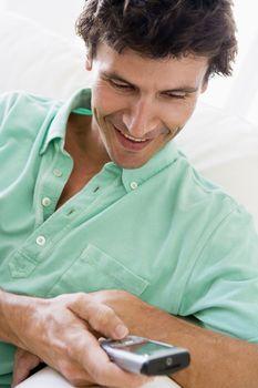 Man indoors text messaging.