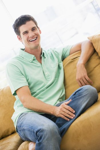 Man sitting in living room laughing