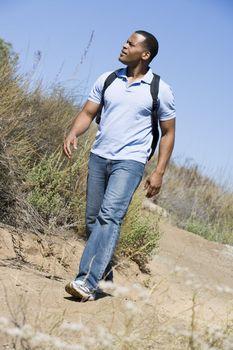 Man walking on path to beach