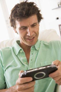 Man in living room playing handheld videogame smiling