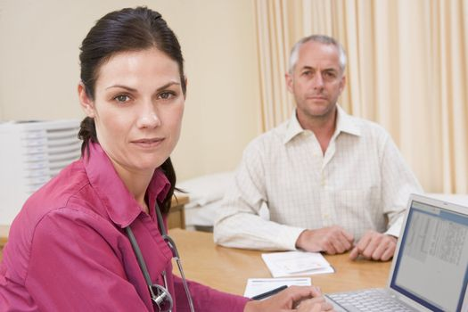 Doctor with laptop and man in doctor's office frowning