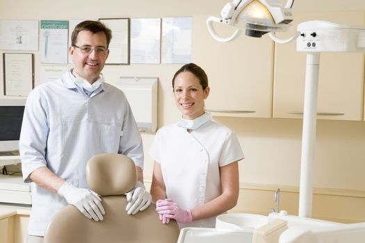 Dentist and assistant in exam room smiling