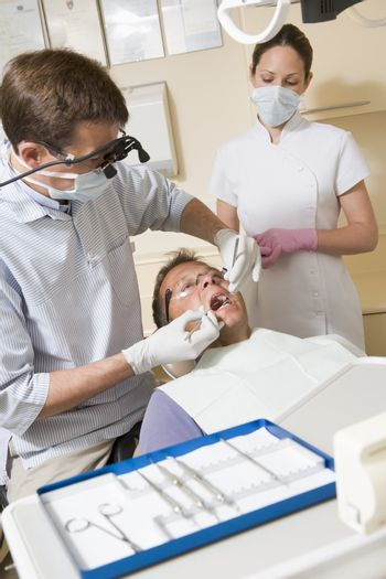 Dentist and assistant in exam room with man in chair
