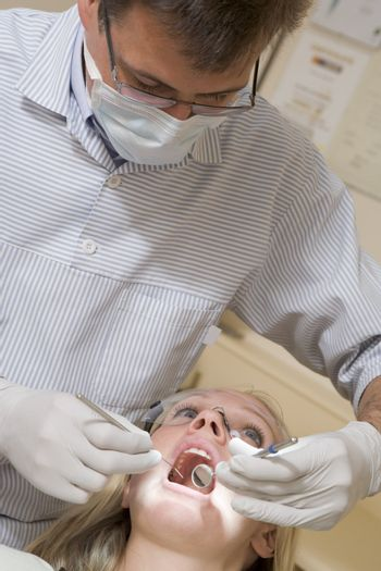 Dentist in exam room with woman in chair