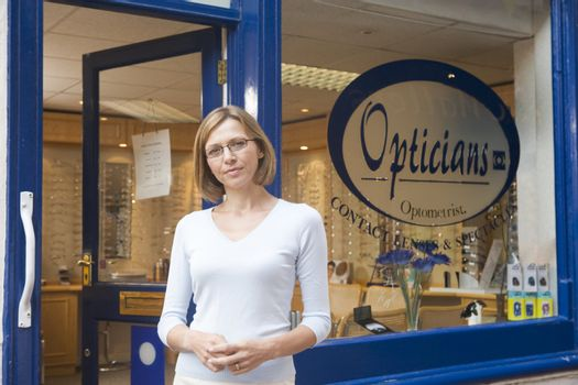 Woman standing at front entrance of optometrists