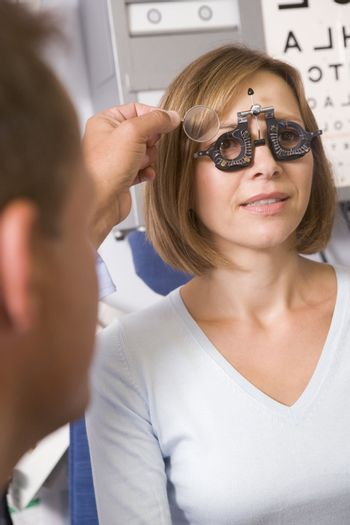 Optometrist in exam room with woman in chair