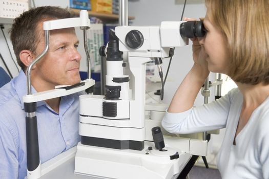 Optometrist in exam room with man in chair