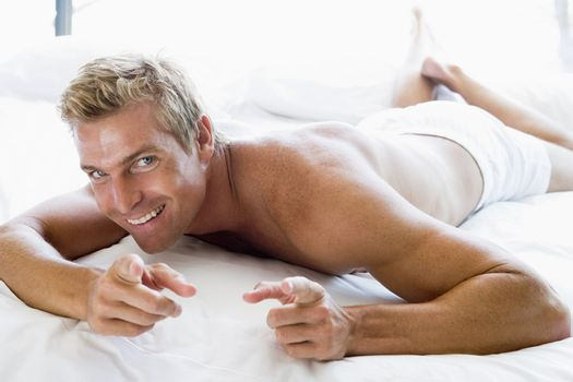 Man lying in bed pointing and smiling