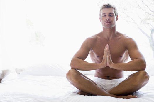 Man sitting on bed meditating