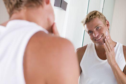 Man in bathroom applying face cream smiling