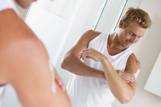 Man in bathroom applying lotion and smiling