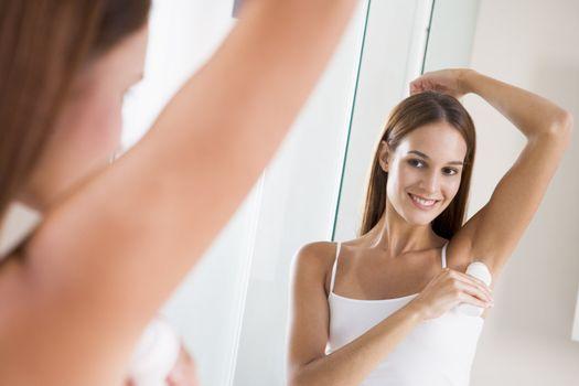 Woman in bathroom applying deodorant and smiling