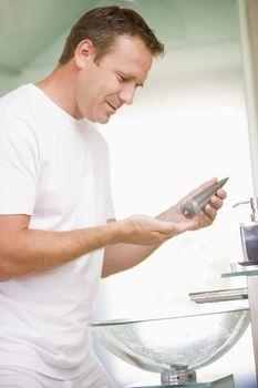 Man in bathroom applying aftershave