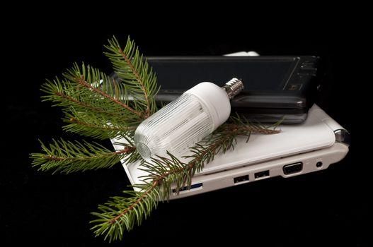 netbooks and energy saving light bulb on black background