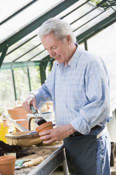 Man in greenhouse putting soil in pot smiling