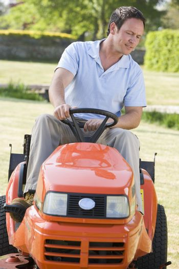 Man outdoors driving lawnmower