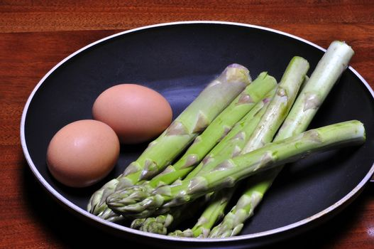 asparagus and eggs in a pan on a round table