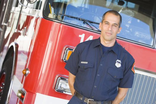 Portrait of a firefighter by a fire engine